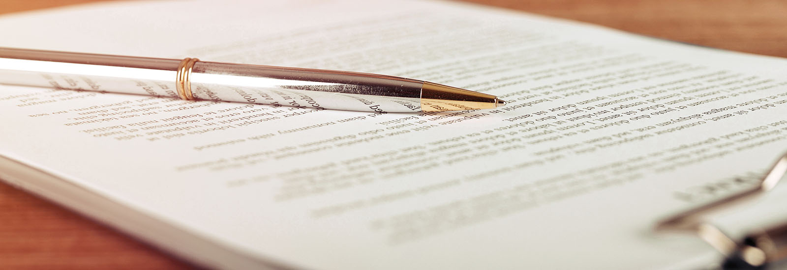 Pen lying on a contract or application form, wide angle view.